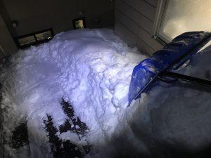 傾斜屋根の雪下ろし作業中