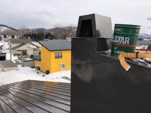 屋根の上から煙突掃除
