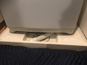 洗濯機の下に排水口が設置されている